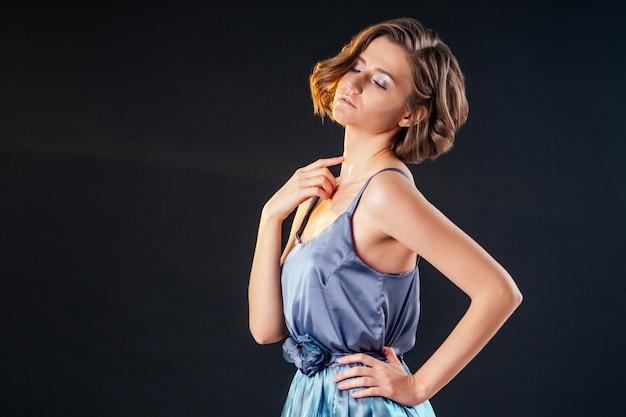 Porträt einer jungen frau im windigen blauen kleid. schönes mädchen mit kreativem make-up und kurzhaarfrisur