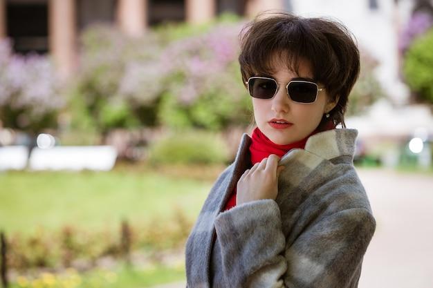 Porträt einer jungen frau in der sonnenbrille im mantel vor dem hintergrund der isaakskathedrale