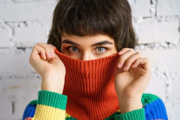 Porträt einer jungen frau in einem bunten pullover, die ihr gesicht mit einem pullover bedeckt. das konzept der schüchternheit