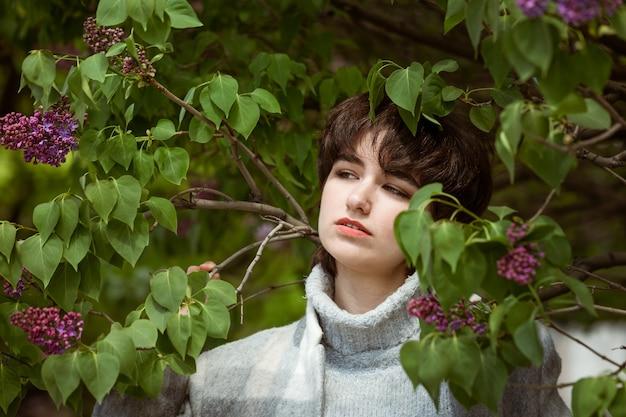Porträt einer jungen frau in einem fliederbusch an einem sonnigen frühlingstag