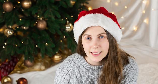 Porträt einer jungen frau in einem grauen pullover und weihnachtsmannhut sitzt nahe einem weihnachtsbaum
