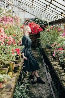 Porträt einer jungen frau in einem grünen kleid in einem gewächshaus mit roten und rosa blühenden azaleen