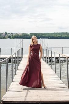 Porträt einer jungen frau in einem roten kleid in der nähe von teich, entspannen und genießen sie den heißen sommertag, lifestyle