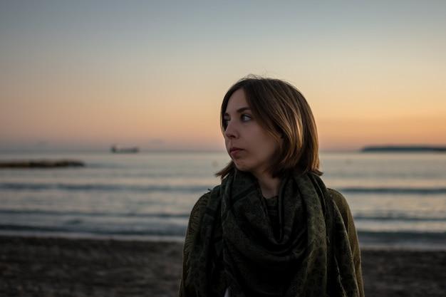 Porträt einer jungen frau in einem strand bei sonnenuntergang