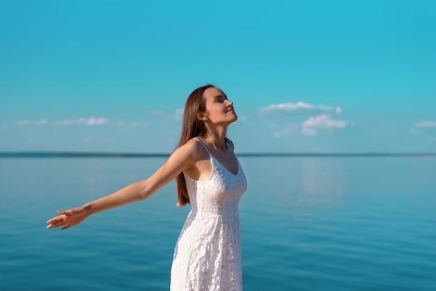 Porträt einer jungen frau in einem weißen kleid mit offenen händen, die saubere seeluft am ufer, frische luft, freiheit, ökologie atmen