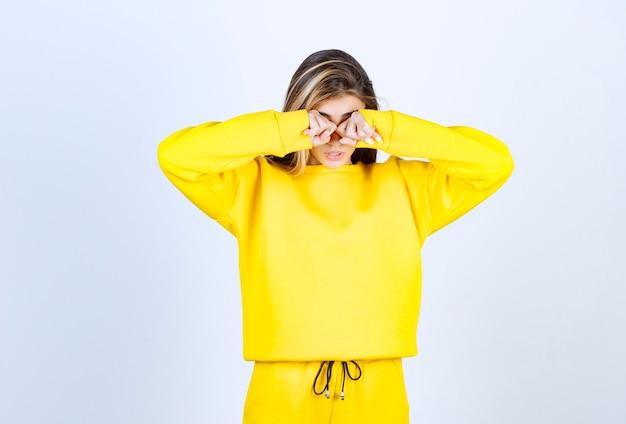 Porträt einer jungen frau in gelbem outfit, die über etwas schlimmes weint