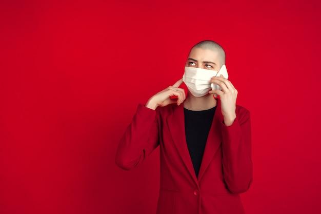 Porträt einer jungen frau in rotem anzug und weißer gesichtsmaske, die isoliert auf rotem studio telefoniert
