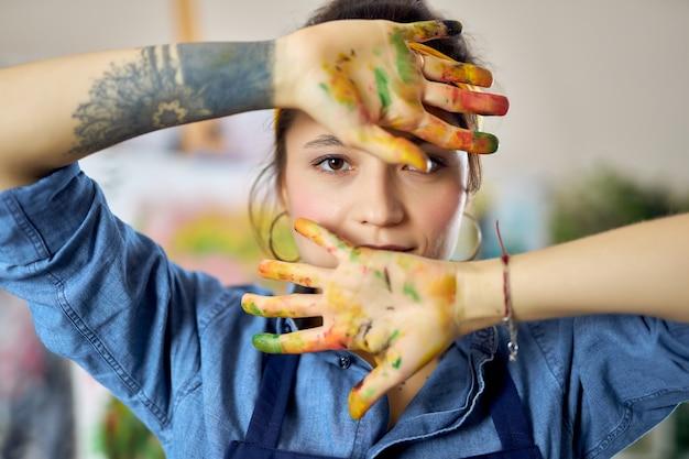 Porträt einer jungen frau in schürze, die in die kamera schaut und ihre hände beim malen in farbe zeigt