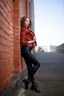 Porträt einer jungen frau in schwarzen leggings und roter lederjacke, die in der nähe der roten backsteinmauer steht