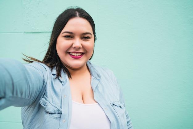 Porträt einer jungen frau in übergröße, die ein selfie macht, während sie im freien gegen hellblaue wand steht.