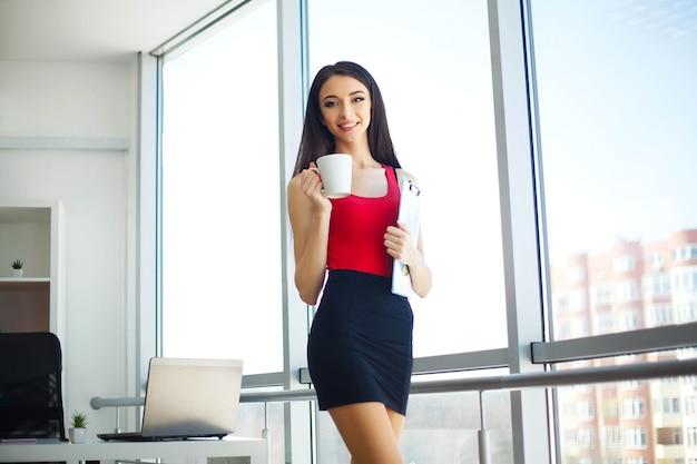 Porträt einer jungen frau kleidete in der roten stellung am großen fenster im hellen modernen büro und im lächeln an.