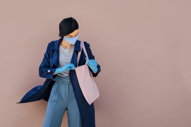 Porträt einer jungen frau mit baumwollmaske und medizinischen handschuhen mit einkaufstasche auf der straße während des ausbruchs von covid 19. schutz in der prävention des coronavirus.