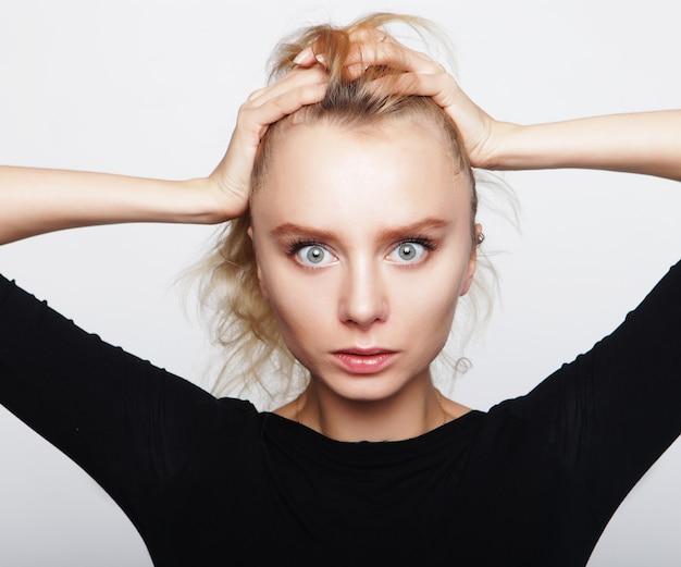 Porträt einer jungen frau mit blondem haar in einem schwarzen hemd auf einem weißen hintergrund. eine frau ohne make-up. modelltest. model.