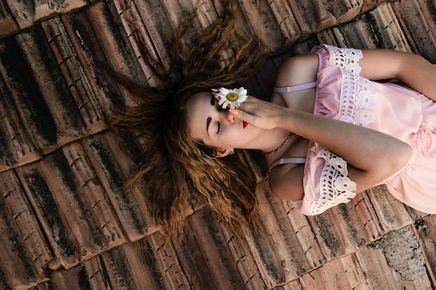 Porträt einer jungen frau mit blume. gesicht der frau mit make-up und frisur