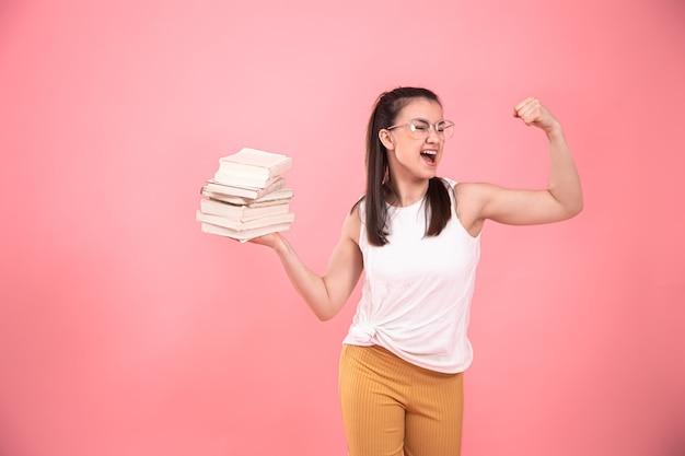 Porträt einer jungen frau mit brille auf rosa mit büchern in ihren händen