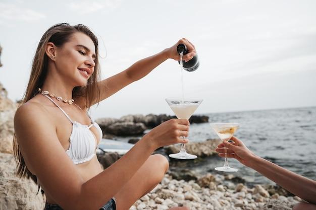 Porträt einer jungen frau mit cocktailglas, die an einem strand chillt, nahaufnahme