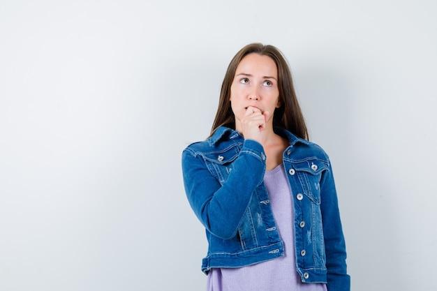Porträt einer jungen frau mit der hand am kinn, die in t-shirt, jacke und nachdenklicher vorderansicht aufschaut