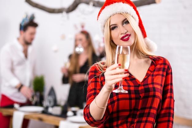 Porträt einer jungen frau mit einem glas champagner zu hause im vordergrund schöne blondine in einem ...