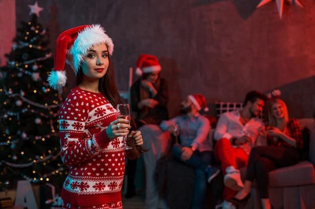 Porträt einer jungen frau mit einem glas champagner zu hause im vordergrund. schöne brünette in einer weihnachtsmütze, rotes kostüm mit hirschen