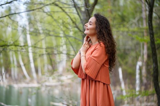 Porträt einer jungen frau mit einem lächeln im gesicht, glückliche gefühle. ein mädchen mit langen, gewellten locken in einem kleid im sommer in der natur, in einem wald an einem see, stand in der nähe einer straße und büschen