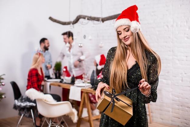Porträt einer jungen frau mit einer goldenen geschenkbox zu hause im vordergrund schöne blondine in einem weihnachtsmann ...