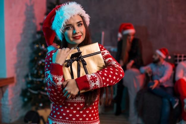 Porträt einer jungen frau mit einer goldenen geschenkbox zu hause im vordergrund. schöne brünette in einer weihnachtsmütze, rotes kostüm mit hirschen