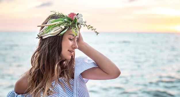 Porträt einer jungen frau mit einer zusammensetzung der blumen auf ihrem kopf vor dem hintergrund des ozeans bei sonnenuntergang.