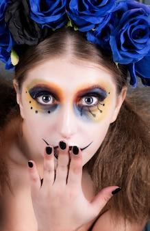 Porträt einer jungen frau mit halloween bilden mit blauen blumen.