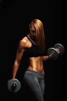 Porträt einer jungen frau mit hanteln in fitten händen posiert mit einem sport-bh vor schwarzem hintergrund. entschlossener athlet im studio. kopieren sie platz, schwarzer hintergrund, sportbanner.