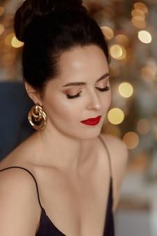 Porträt einer jungen frau mit modischer frisur und hellem make-up bereit für die neujahrsparty.