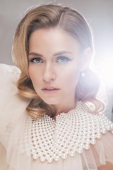 Porträt einer jungen frau mit perlenkragen, ohrring, perfektem make-up am abend und stilvoller wellenfrisur in studiobeleuchtung. foto in hoher qualität