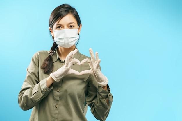 Porträt einer jungen frau mit schützender medizinischer maske und handschuhen, die herzgeste zeigen