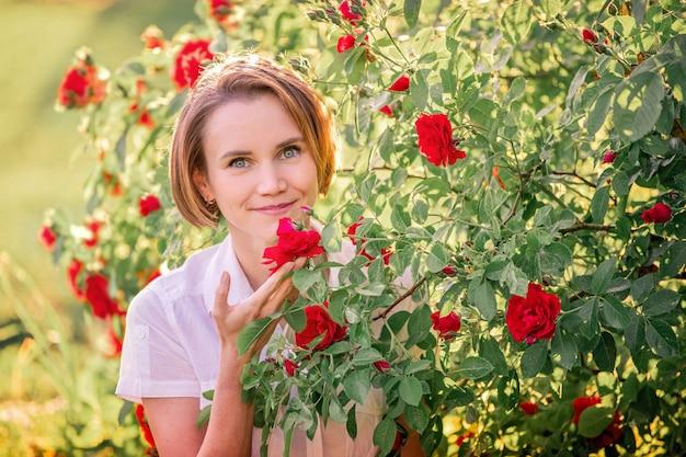 Porträt einer jungen frau unter roten rosen im hinteren sonnenlicht