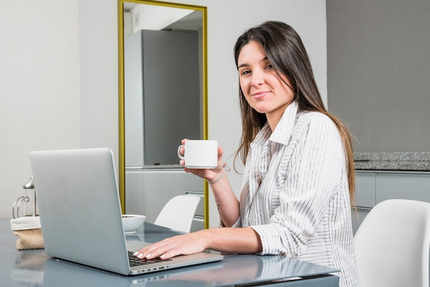 Porträt einer jungen frau, welche die kaffeetasse sitzt am frühstückstische mit laptop hält