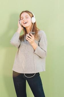 Porträt einer jungen frau, welche die musik auf kopfhörer gegen tadellosen grünen hintergrund genießt