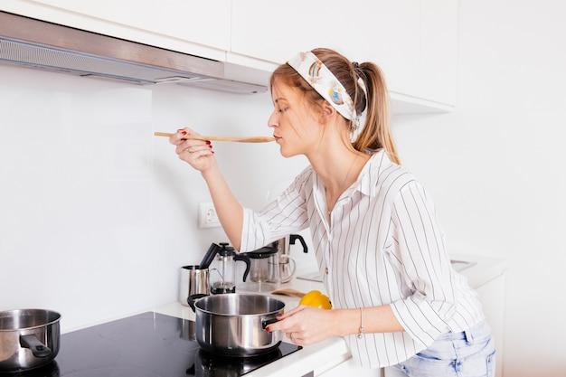 Porträt einer jungen frau, welche die suppe beim vorbereiten in der küche schmeckt
