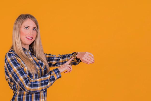 Porträt einer jungen frau, welche die zeit auf armbanduhr gegen einen orange hintergrund überprüft