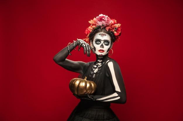 Porträt einer jungen frau wie santa muerte saint death oder sugar skull mit hellem make-up. frau auf rotem studiohintergrund mit exemplar isoliert. feiern von halloween oder tag der toten.