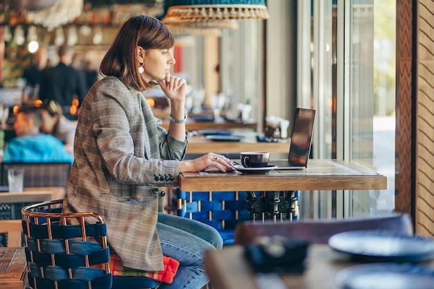 Porträt einer jungen freiberuflerin, die laptop-computer für fernjob verwendet, während sie im café sitzt.