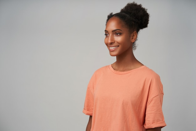 Porträt einer jungen, fröhlichen, dunkelhäutigen, brünetten frau, die mit einem charmanten lächeln positiv nach vorne schaut, während sie mit den händen nach unten auf grau steht