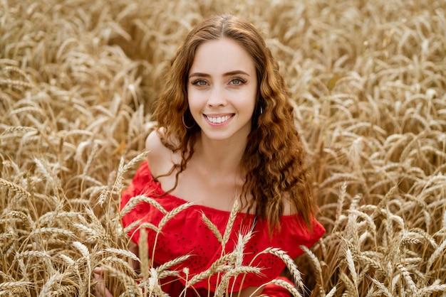 Porträt einer jungen fröhlichen frau mit gewelltem haar in einem roten kleid sitzt in einem weizenfeld