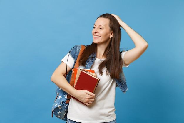 Porträt einer jungen fröhlichen studentin mit rucksack, die sich berührt und korrekter frisur beiseite schaut, schulbücher auf blauem hintergrund isoliert halten. bildung im hochschulkonzept der high school.