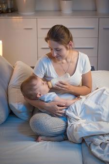 Porträt einer jungen fürsorglichen mutter, die ihrem baby nachts im bett eine flasche mit milch gibt