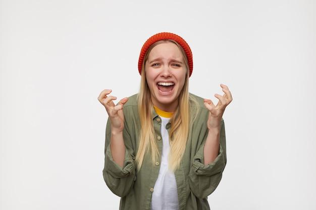 Porträt einer jungen, genervten, langhaarigen, weißköpfigen frau, die emotional ihre hände hebt, während sie zerlegt auf blau steht