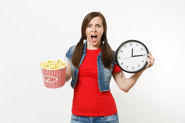 Porträt einer jungen gereizten brünetten frau in freizeitkleidung, die filmfilm sieht, einen eimer popcorn und einen runden wecker hält und auf weißem hintergrund schreit. emotionen im kinokonzept.