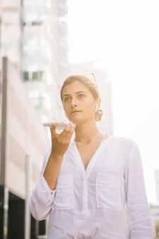 Porträt einer jungen geschäftsfrau, die am handy durch sprecher spricht