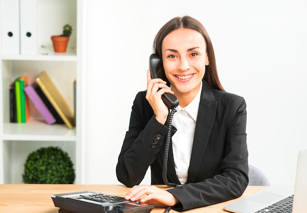 Porträt einer jungen geschäftsfrau, die am telefon betrachtet kamera spricht