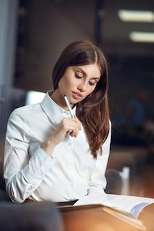 Porträt einer jungen geschäftsfrau, die an ihrem arbeitsplatz im büro sitzt.