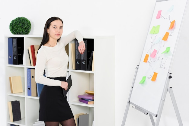 Porträt einer jungen geschäftsfrau, die auf regal am arbeitsplatz sich lehnt
