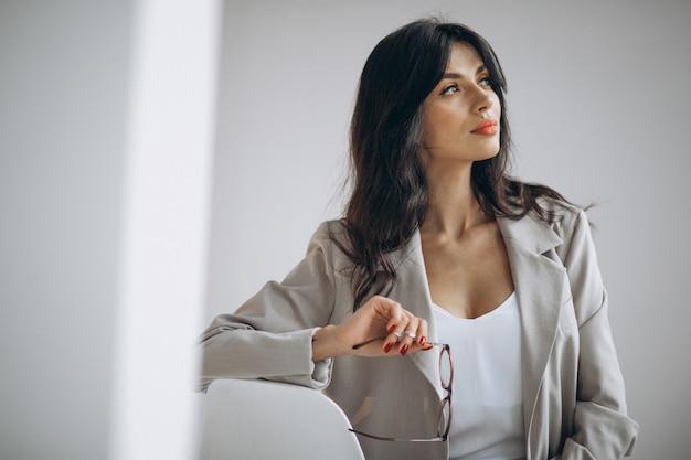 Porträt einer jungen geschäftsfrau, die im büro sitzt